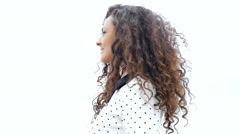 Portrait of happy young woman with curly hair on white background, slow motion - stock footage
