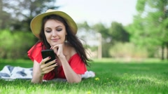 Young woman using mobile phone with empty red screen lying on the green grass. - stock footage