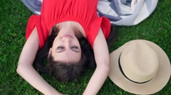 Relaxing in grass. Top view of beautiful young woman on the green grass - stock footage