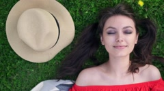 Relaxing in grass. Top view of beautiful young woman on the green grass Stock Footage