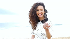 Young woman gesturing follow me and running on the beach, slow motion - stock footage