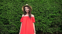 SLOW MOTION. Beautiful happy model standing playful in red dress on nature Stock Footage