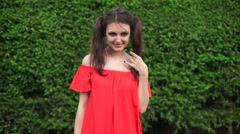 SLOW MOTION. Beautiful happy model standing playful in red dress on nature - stock footage