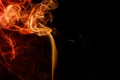 Abstract yellow red smoke from aromatic sticks. - stock photo