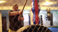 Boxer doing exercise with hummer and tire in the cage in the gym. 4k Stock Footage