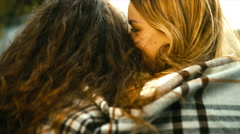 Young Caucasian teen girls standing wrapped in a plaid. Love, friendship concept Stock Footage