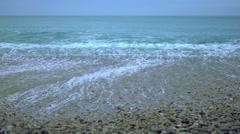 Foamy ocean wave rolling ashore in slowmotion, pebble beach under foggy sky Stock Footage