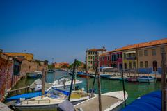 MURANO, ITALY - JUNE 16, 2015: Various boats parking on Murano canals outside of - stock photo