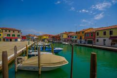 MURANO, ITALY - JUNE 16, 2015: Wooden port at Murano city, parking boats in - stock photo