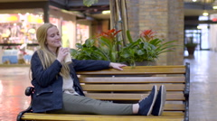Teen Takes A Break, Relaxes On Mall Bench And Sips Her Coffee Drink Stock Footage