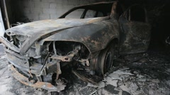 Pan footage of burned out car in garage Stock Footage