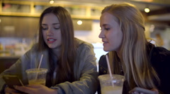 Closeup Of Teens Drinking Coffee, And Looking At A Smart Phone, In Coffee Shop Stock Footage