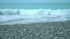Turbulent foamy sea waves splashing ashore on pebble beach in slowmotion Stock Footage