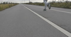 A man in sneakers runs on the asphalt outside the city. - stock footage