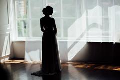 silhouette of a girl at the window - stock photo