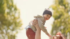 Happy young mather play with smiling baby and throw upwards on nature Stock Footage