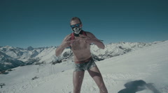 Snowboarder riding in shorts in high mountains Stock Footage