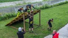 Helping members in the team jump off a hurdle Stock Footage