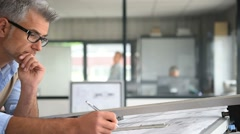 Architect sitting at drawing table in office - stock footage
