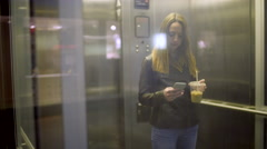 Teen Texts On Her Phone, She Rides A Glass Elevator Down A Level In Mall, Exits Stock Footage