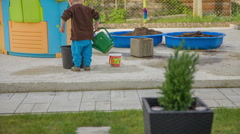 Boy is playing in the garden with a water can Stock Footage