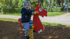 Sitting on a wooden horse in the park Stock Footage
