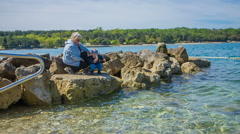 Standing on the rocks and throwing stones into the sea Stock Footage