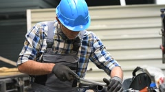 Metalworker with hardhat working piece of metal - stock footage
