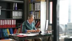 Businessman sitting in office working on desktop Stock Footage
