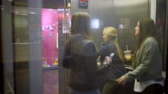 Group Of Teen Friends Get On A Glass Elevator At The Mall, Go Up Stock Footage