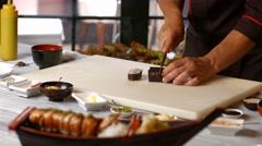 Man's hand cutting sushi rolls. Stock Footage