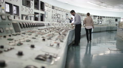 4K Workers in power plant control room, pressing switches on control panel Stock Footage