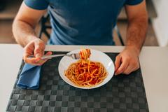 Young man eating spaghetti bolognese. Close up. - stock photo