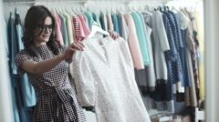 Beautiful girl trying dress near mirror in room Stock Footage