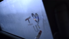 "Teen Girl Writes ""I Heart U!"" On Car Window, Cars Pass By In Background Stock Footage"