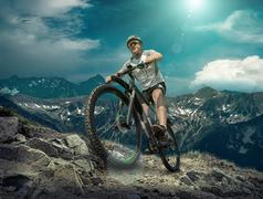 Man in helmet and glasses stay on the bicycle under sky with clo - stock photo
