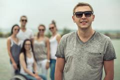 Young people on the pier with them disabled friend. - stock photo