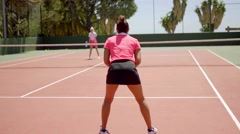 Two fit young women enjoying a game of tennis Stock Footage