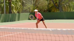 Attractive young woman enjoying a game of tennis Stock Footage