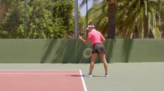 Young woman about to serve in a tennis match Stock Footage
