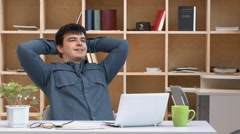 Young guy working at his laptop, leans back in chair, pleased with the result Stock Footage