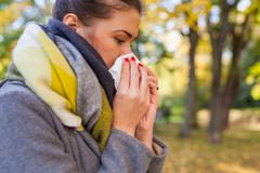Young girl is blowing her nose. She is cold. Autumn time. Stock Photos