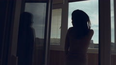 Silhouette of girl in the morning looking out the window and straightens her Stock Footage