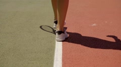 Young female tennis player walking on the baseline Stock Footage
