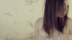 Young brunette wears on a cardigan and gets out of the bed - stock footage