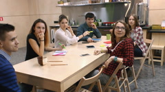 Young people communicate with each other at the table, happily and easily Stock Footage