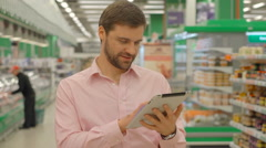 Man holding tablet in hypermarket store - stock footage