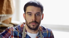 Workman in checkered shirt and apron at workshop Stock Footage