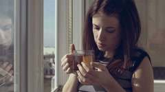 Seductive woman on the balcony of the house and drinking hot tea Stock Footage