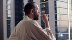 Young man in bathrobe brushing his teeth on balcony Stock Footage